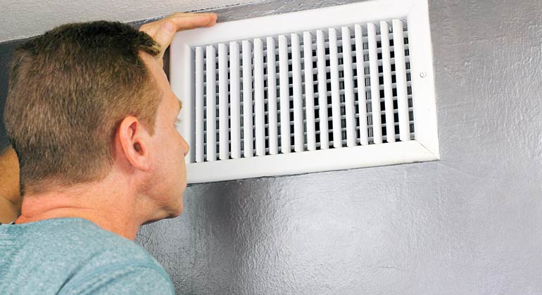 man inspecting air duct